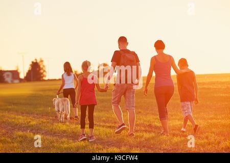 El verano en el campo. las siluetas de la familia con el perro en el viaje al atardecer.
