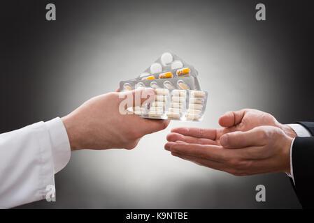 Close-up de la mano de un médico dando diversas medicinas al paciente