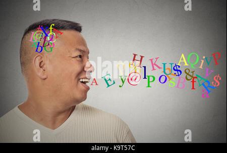 Vista lateral retrato joven apuesto hombre hablando con las letras del alfabeto que sale de la boca abierta aislada pared gris de fondo. rostro humano expresión emot