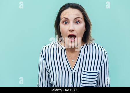 Wow! Sorprendido y consternado hermosa mujer adulta mirando a la cámara con cara de escandalizado. aislado sobre fondo de color azul claro.