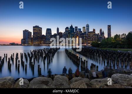 Los rascacielos de Manhattan al atardecer y pilotes de madera del puente de Brooklyn Park. Manhattan, Ciudad de Nueva York Foto de stock