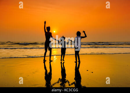 Las siluetas del grupo de niños bailando en la playa al atardecer. Foto de stock