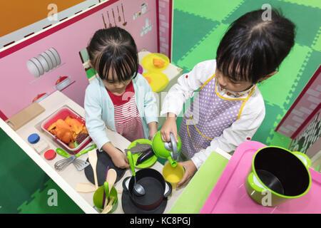 Chino asiática niñas jugar un papel en la cocina a patio interior