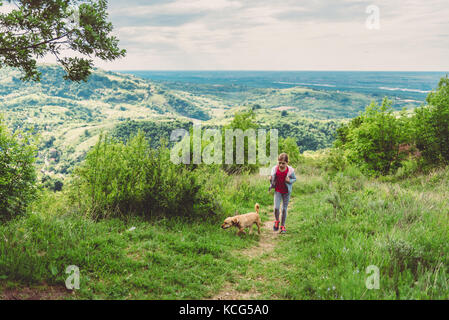 Chica y su perro caminando por un sendero de trekking