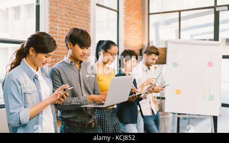 Multiétnica diverso grupo de jóvenes adultos felices utilizando la tecnología de la información, dispositivos gadget juntos. equipo creativo, el trabajo en equipo, el concepto de negocios informal