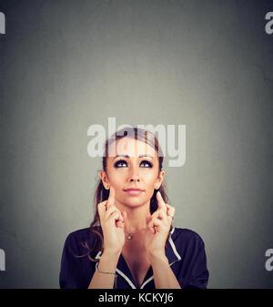 Mujer joven cruzando sus dedos y deseando buena suerte
