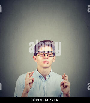 Adolescente hombre cruza los dedos y deseando buena suerte