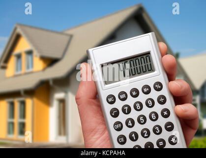 Calculadora con una alta suma en frente de una casa familiar moderna Foto de stock