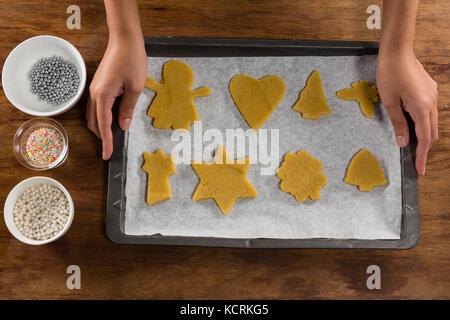 Sección intermedia del hombre sujetando la bandeja para hornear galletas de pan de jengibre completo