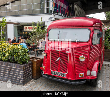 Un vintage Citroën H panel van pintadas de rojo y aparcamos fuera un bar / restaurante en el South Bank de Londres, Inglaterra, Reino Unido.