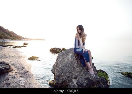 Mujer joven sentado en la playa rock, Odessa, Ucrania