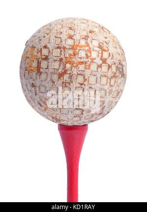 Old golf pelota en un tee rojo aislado sobre un fondo blanco.