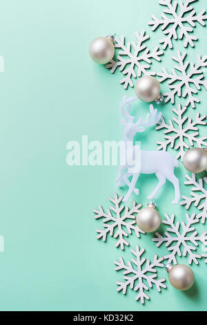 Navidad elegante tarjeta de felicitación de Año Nuevo póster de renos blancos copos de nieve bola sobre fondo azul turquesa claro. Copie el espacio. estilo escandinavo. cr