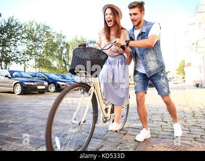 Feliz pareja joven va para un paseo en bicicleta en un día de verano en la ciudad.se divierten juntos.
