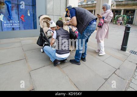 Londres, Inglaterra, Reino Unido. Familia Musulmana en Covent Garden - hombres cuidando de los niños Foto de stock