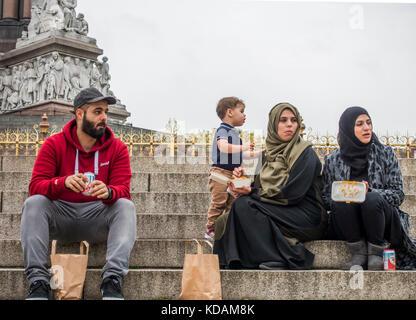 Familia Musulmana, tras un almuerzo para llevar, sentado en escalones que llevan hasta la histórica Albert Memorial, los Jardines de Kensington, Londres W2, Inglaterra, Reino Unido. Foto de stock