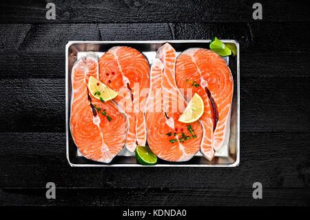 Filetes de salmón en la bandeja de metal sobre tabla de madera negra vista superior