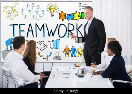 Empresario dando presentación sobre el trabajo en equipo a sus colegas en la oficina