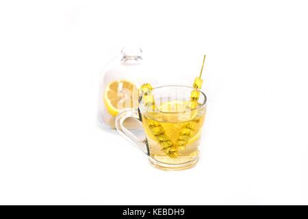 Té caliente con salvia y limón en la jarra de vidrio. Foto de stock