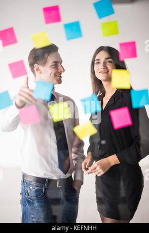 Inicie la planificación de negocio y hacer organización con pareja joven en la oficina moderna interior escribir notas sobre adhesivos Foto de stock