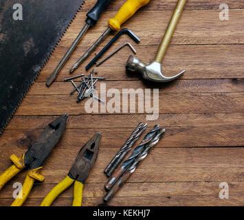 Oxidados y viejos utiliza herramientas de carpintería y garaje sobre un fondo de madera de color marrón claro, mostrando variadas herramientas,con pinzas de metal y vio,brocas metálicas,martillo