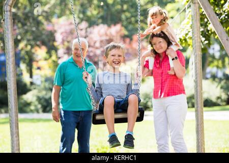 Feliz nieto kid divirtiéndose en swing con viejos abuelos de pie detrás en el parque