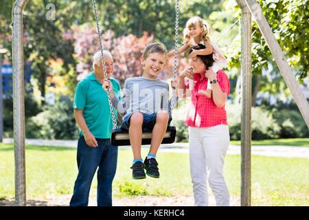 Niño feliz divirtiéndose en swing con abuelos de pie detrás en el parque