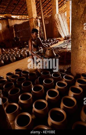 Manos de hacer una vasija de barro en las ruedas de cerámica ,seleccione focus, cerca. potter conformando la olla de barro de terracota en pápula igual, Lady ayudantes en terracota
