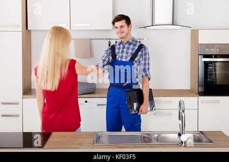 Fontanero y mujer agitando las manos después de las reparaciones en ...