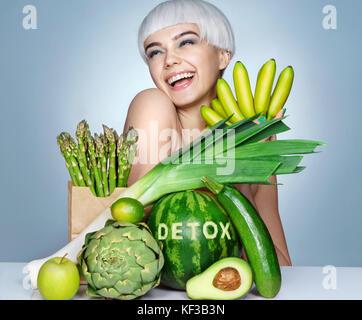 Feliz joven con una abundancia de frutas y verduras. Foto de sonriente chica rubia sobre fondo azul concepto de estilo de vida saludable.