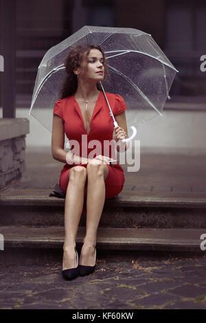 Mujer joven en un elegante vestido rojo esperando que alguien sentado en las escaleras con un paraguas en la lluvia en una calle de la ciudad