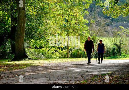 Las parejas ancianas caminar en otoño Sol, sheringham, North Norfolk, Inglaterra