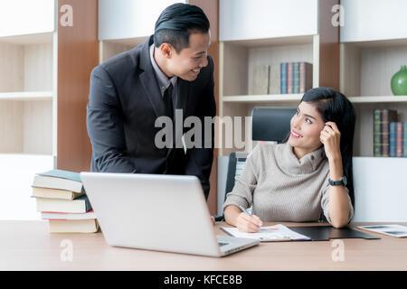 Dos colegas empresario asiático y empresaria utilizando el portátil mientras está trabajando en el nuevo proyecto empresarial, dos jóvenes empresarios profesionales trabajando por Foto de stock