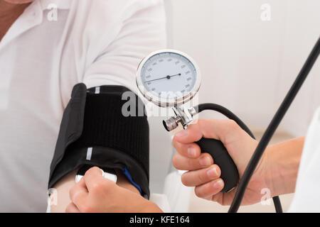Close-up de un médico controlar la presión sanguínea del paciente
