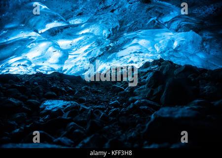 En un estrecho túnel bajo un glaciar en British Columbia, Canadá, el hielo encima se ilumina en color azul del sol brillando a través de las capas de hielo superiores.
