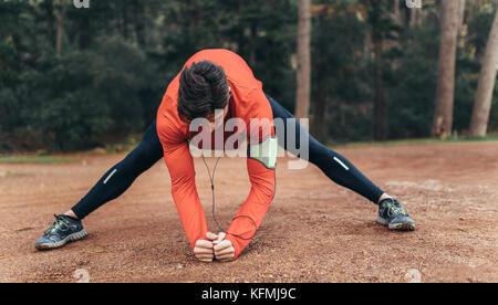 Runner hacer ejercicios de estiramiento en un parque escuchando música. Hombre vestido con auriculares de calentamiento antes de correr.