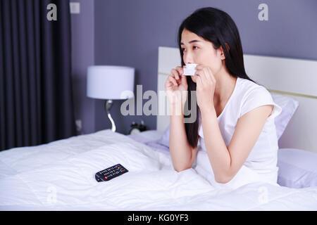 Mujer llorando mientras ve la televisión con control remoto en la cama en el dormitorio