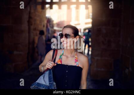 Moda atractiva mujer con gafas de sol y llevar un gran bolso sobre su hombro de compras en la ciudad mirando hacia el lado con una sonrisa