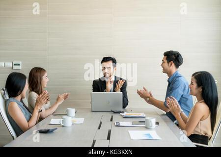 Manos de socios comerciales aplaudiendo al periodista después de escuchar su presentación en reunión.