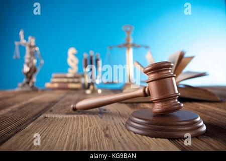 Juez concepto. maceta del juez, la justicia escala y libros sobre un mostrador de madera y fondo azul.