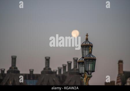 La luna sobre Portcullis House y Old Scotland Yard en amanecer en otoño con lámpara de calle en el puente Westminster
