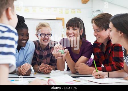 Los estudiantes adolescentes con el profesor en clase de biología