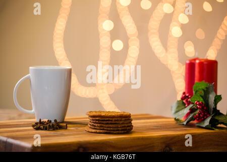 Preciosa imagen cerca de galletas de Navidad sobre una tabla de cortar de madera con algunas velas perfumadas y una copa de whisky / café y algunos canela