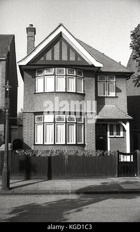 1940, Inglaterra, vista exterior de una casa unifamiliar bien construida en los suburbios. Construido en un estilo tradicional en la era de la preguerra de los años 30 con una bahía redonda y un único vidrio en marcos de madera, que consistía en varias ventanas 'puerta' con ventanas más pequeñas de luz de fanlight encima. La mitad superior de la casa tiene un exterior de guijarros y que está separado y no, semi-separado indicaría que la casa estaba en una zona próspera. Foto de stock
