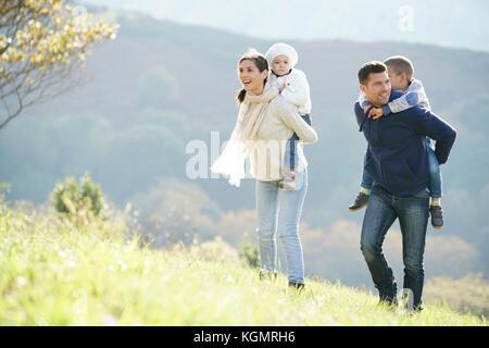 Familia feliz caminar en el campo a fin de semana otoñal