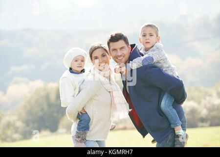 Familia feliz, paseo en piggyback campiña en día otoñal