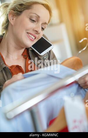 Mujer hablando por teléfono con un amigo, mientras que las compras en tienda de ropa