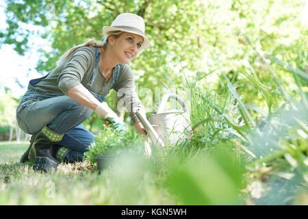 Mujer rubia con sombrero jardinería