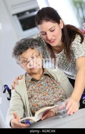 Retrato de anciana en silla de ruedas con la casa del cuidador Foto de stock
