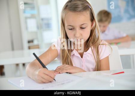 Linda colegiala escrito en el portátil, en el aula